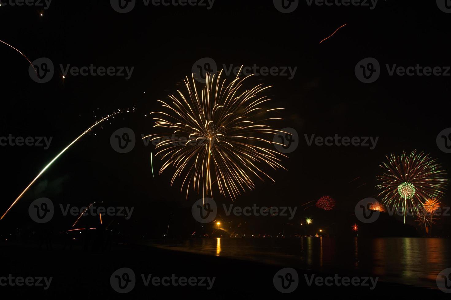 beau feu d'artifice célébrant le nouvel an sur la plage photo