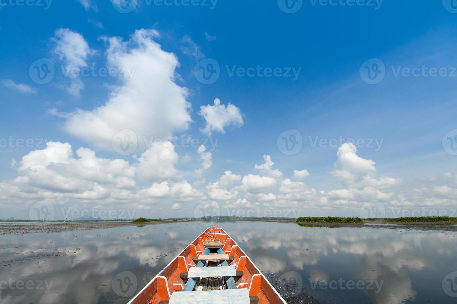 bateau dans le lac avec un ciel bleu nuageux photo