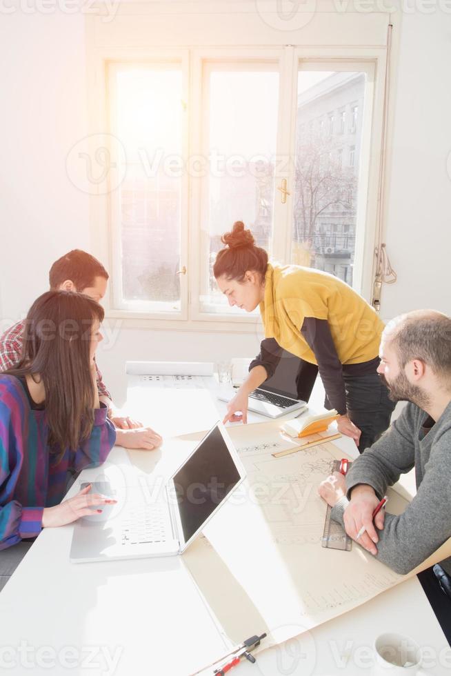 jeune groupe de personnes discutant des plans d'affaires photo