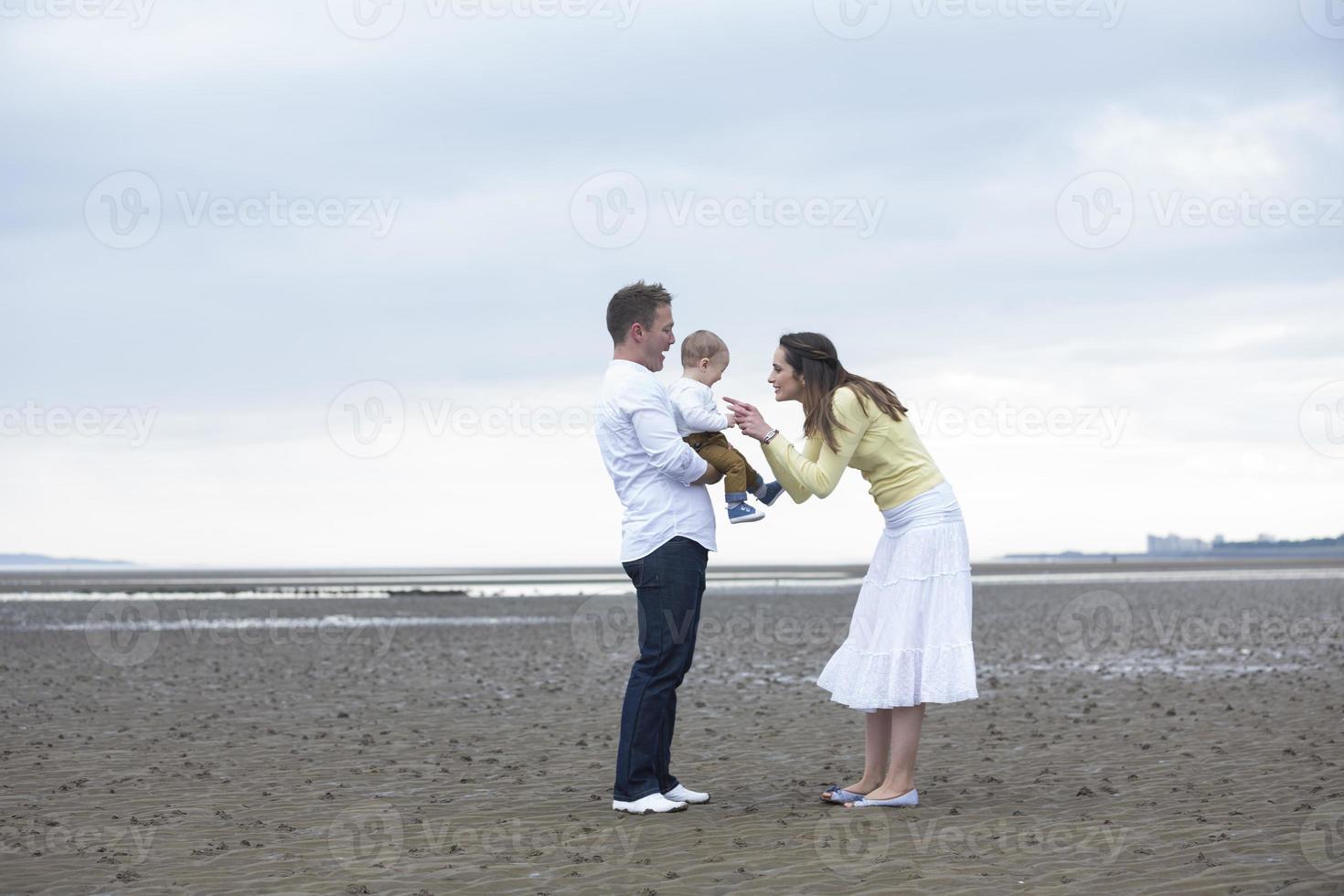 jeune famille ensemble sur la plage. photo
