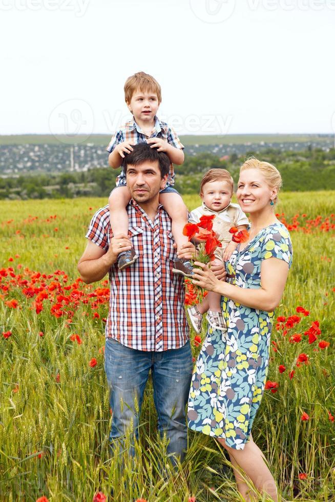 jeune famille heureuse de quatre s'amuser ensemble en plein air. photo