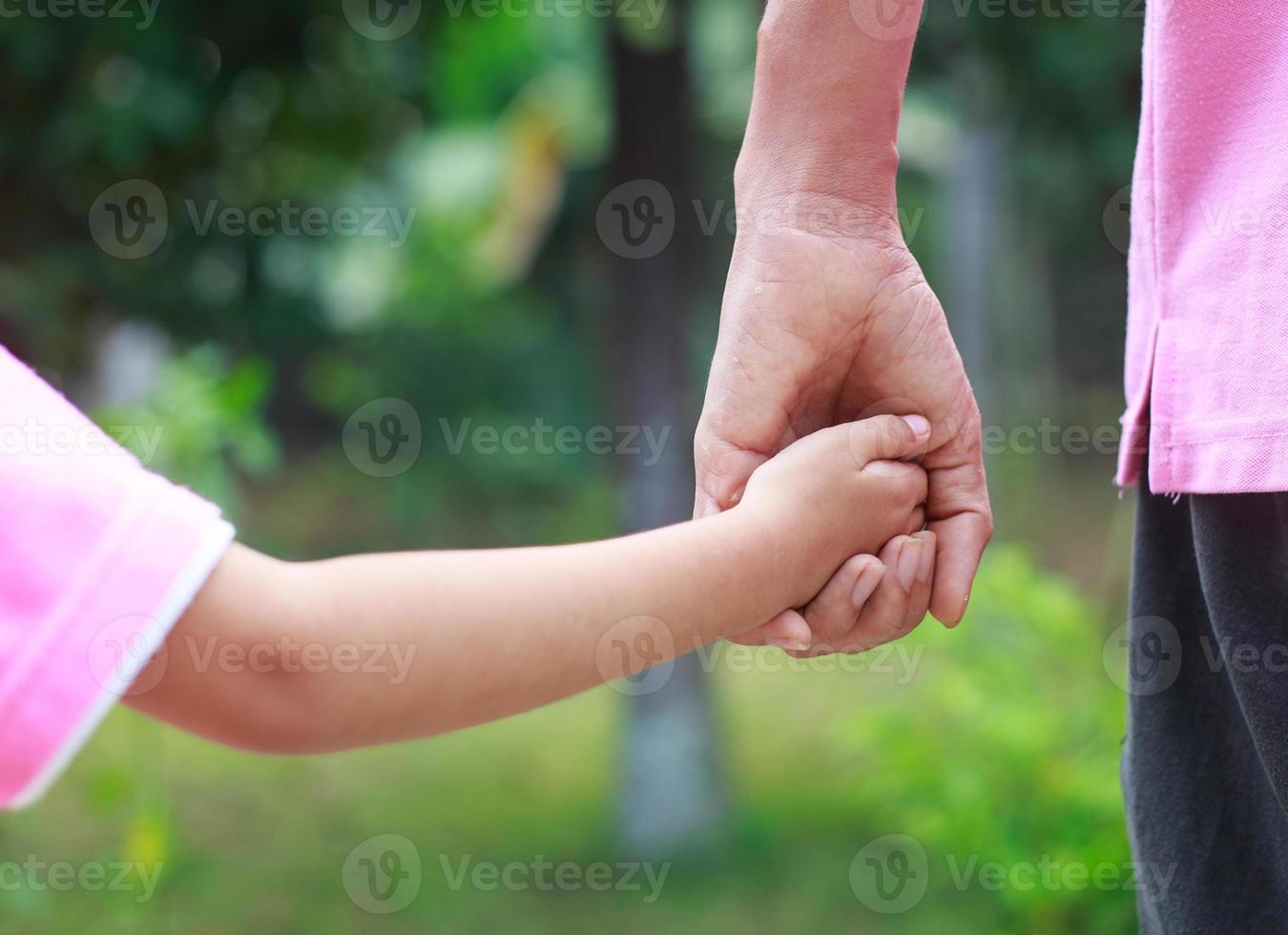 père tenir la main de l'enfant photo