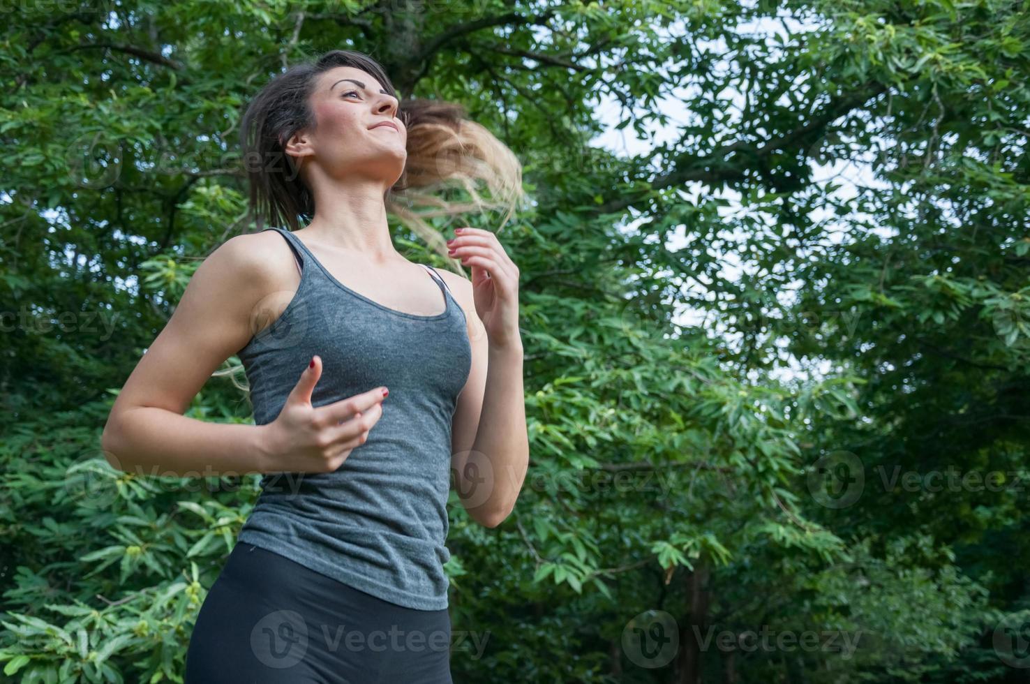 athlète féminine en cours d'exécution sur le parc photo