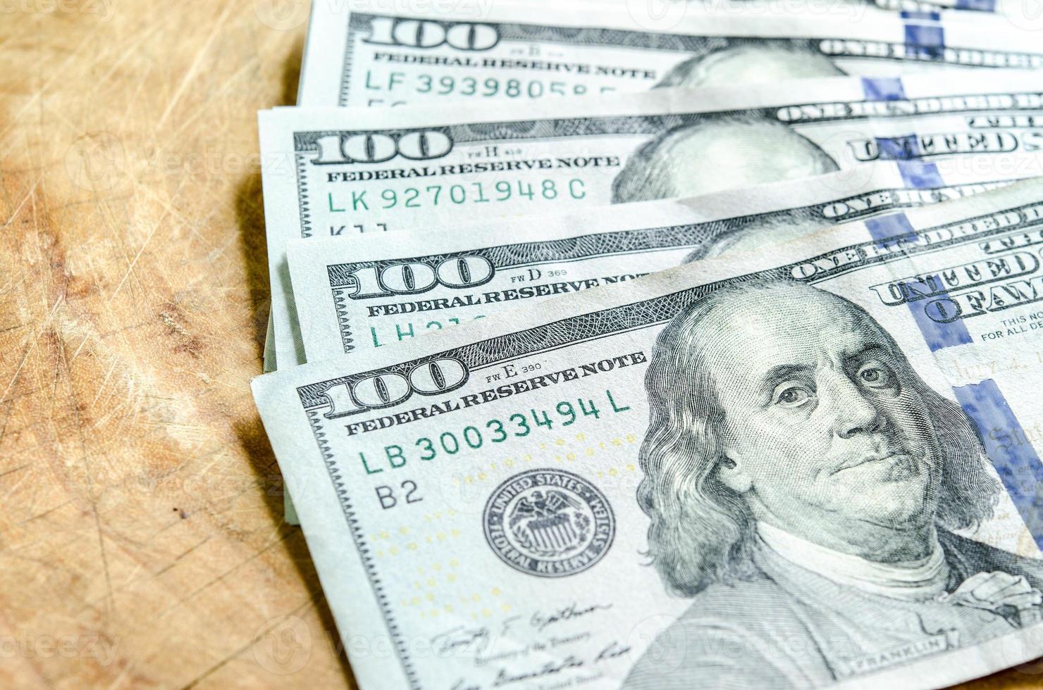 pile de billets de cent dollars gros plan sur fond de bois. photo