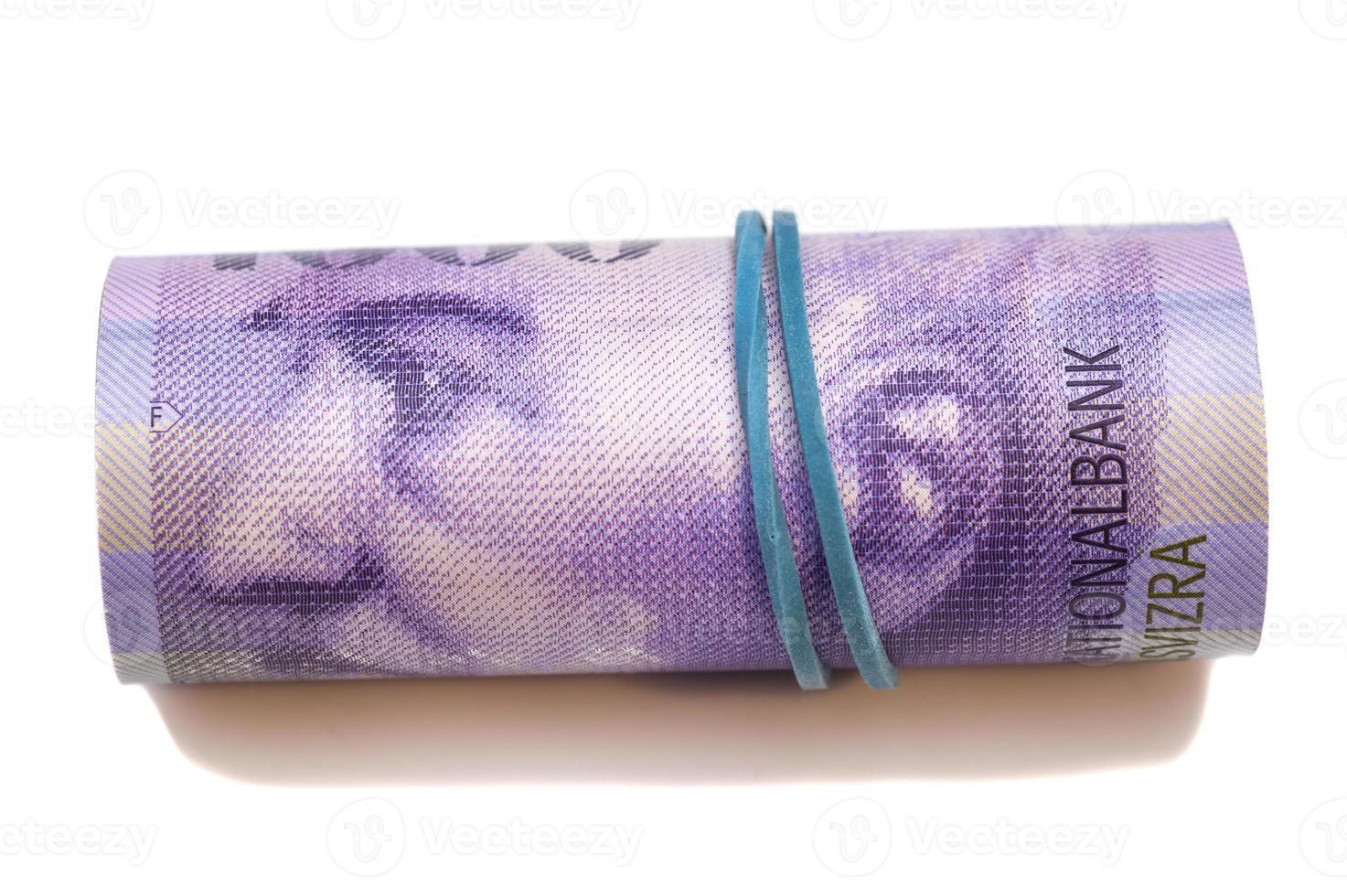 mille francs suisses en rouleau sur fond blanc photo