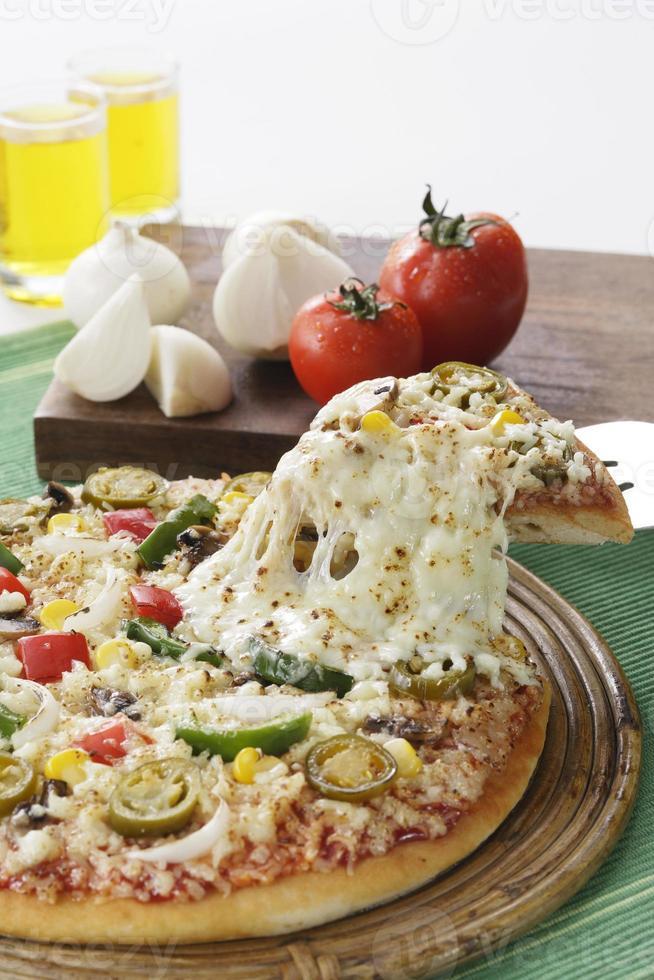 délicieuse pizza avec des légumes qui l'entourent dans le cadre. photo