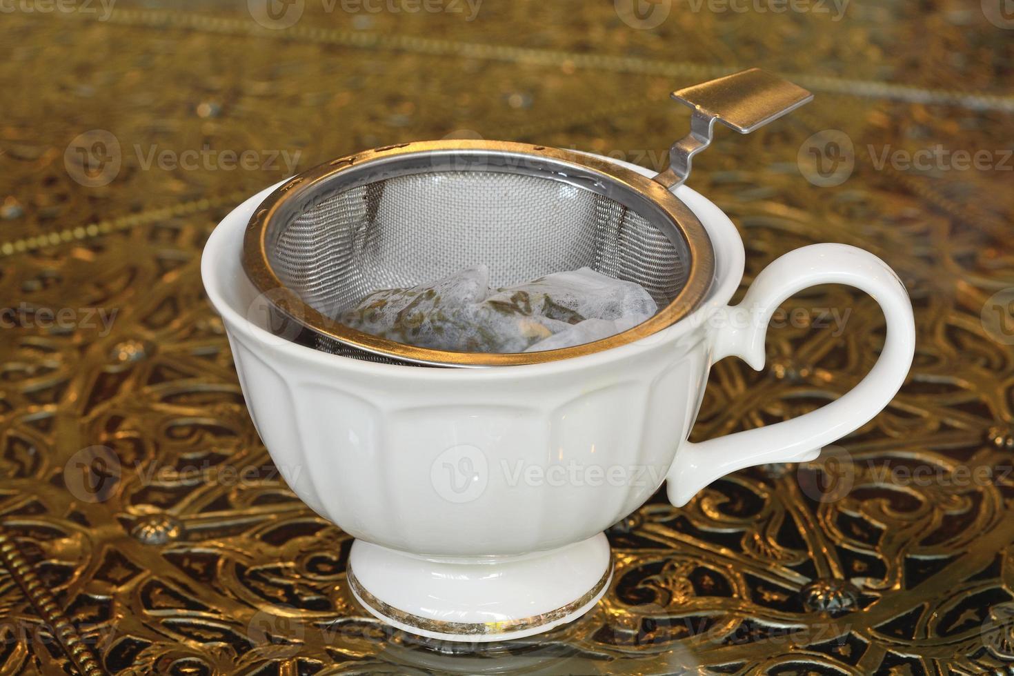 passoire à thé vintage et thé prêt en tasse photo