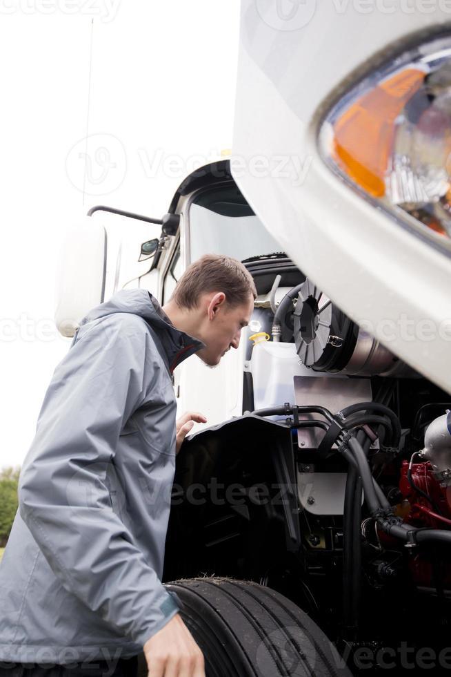 Chauffeur de camion inspectant le moteur semi-remorque blanc photo
