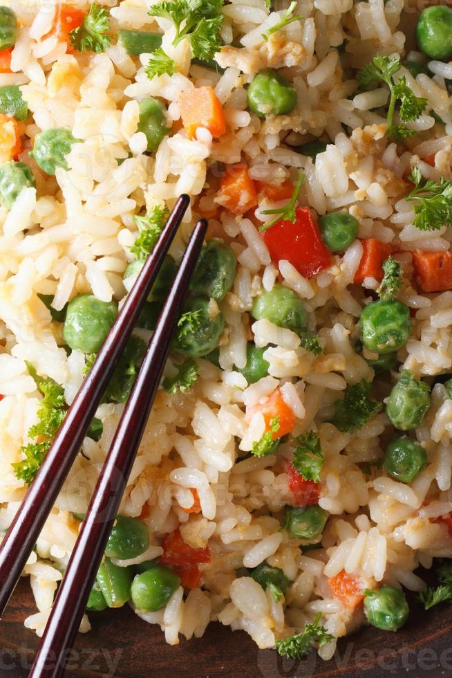 riz frit avec oeuf, pois, carottes macro vue de dessus verticale photo