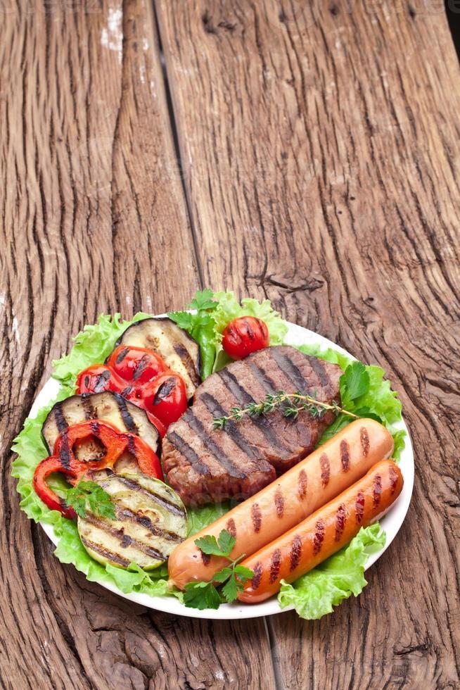 steak grillé, saucisses et légumes. photo