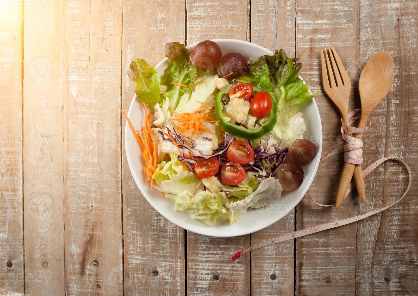 Salade fraîche saine, ustensile et ruban à mesurer sur bois backgrou photo