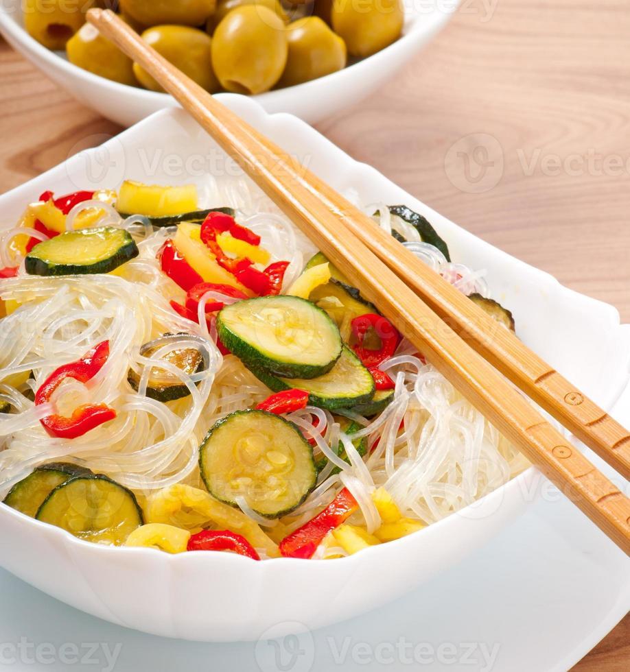 nouilles de riz et légumes sur une plaque blanche photo