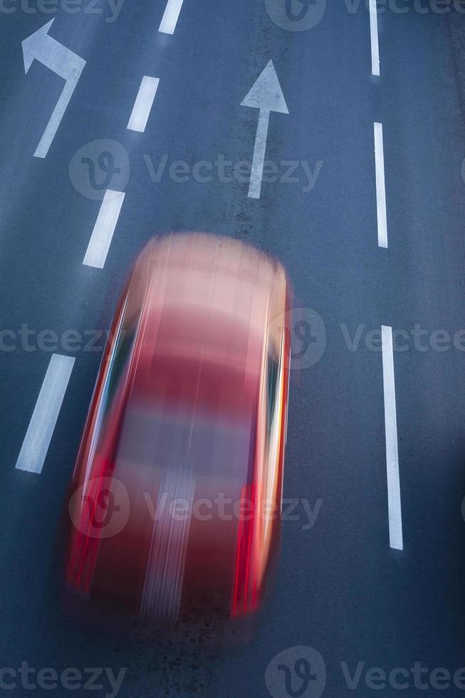 voiture rouge floue, danger de vitesse en ville. photo