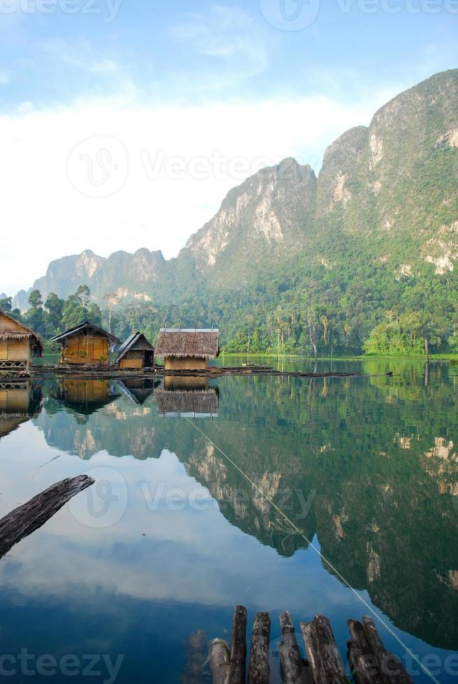 cabane tropicale au bord du lac et bateau en bois photo
