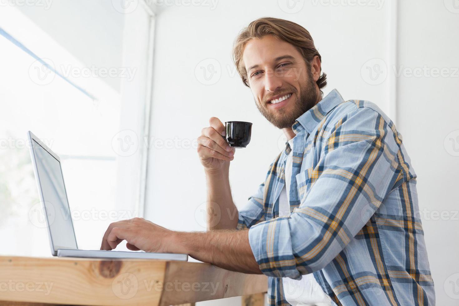 homme décontracté à l'aide d'ordinateur portable, boire un expresso photo