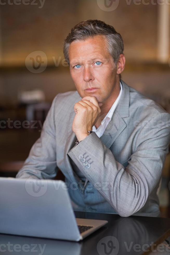homme d'affaires sérieux à l'aide de son ordinateur portable photo