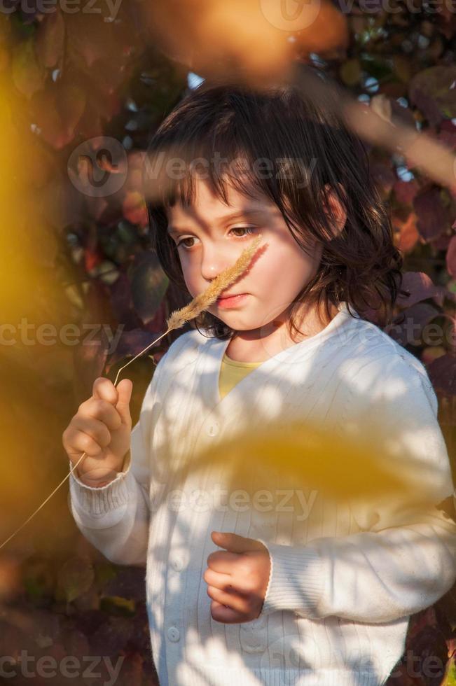 rêveuse petite fille garder tige d'herbe près du nez photo
