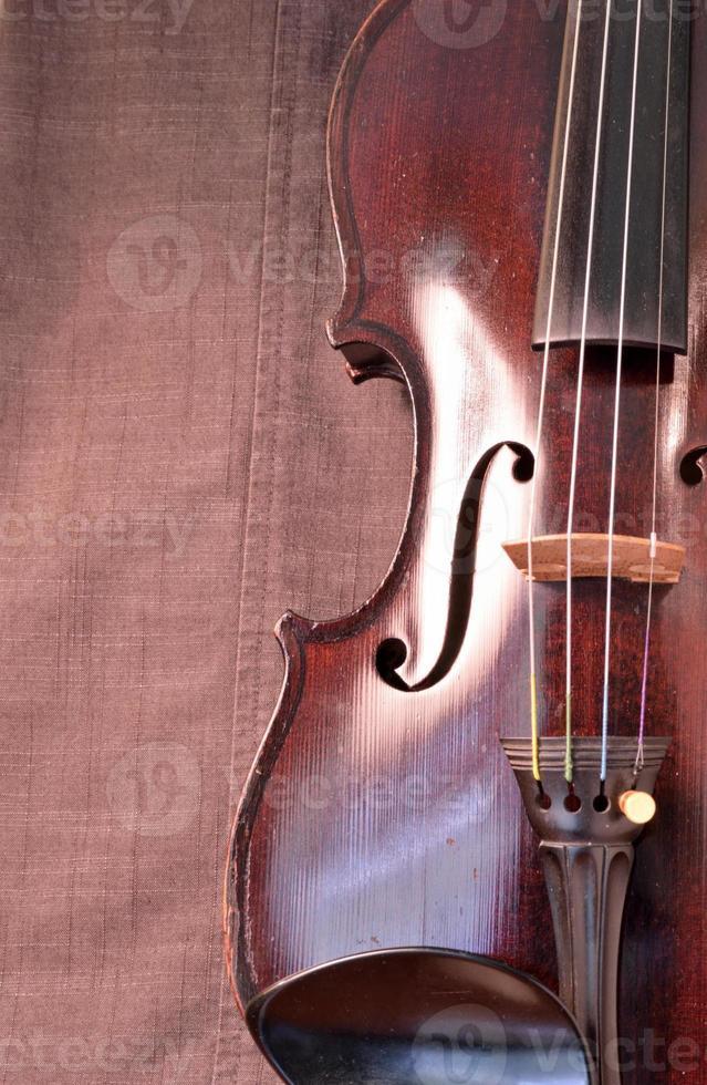 Gros plan du violon antique sur fond de tissu gris vertical photo