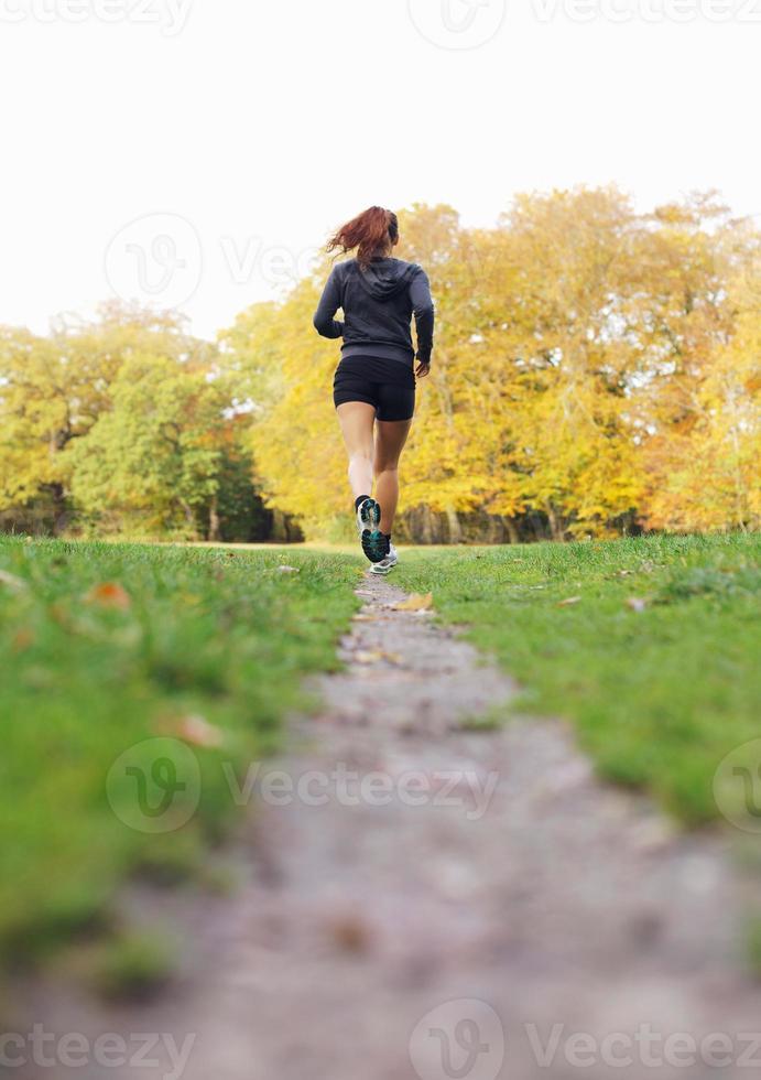 athlète féminine en forme et en bonne santé en cours d'exécution dans le parc photo