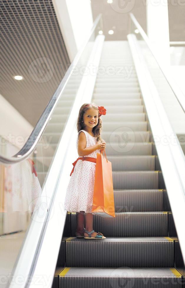 heureuse petite fille avec sac à provisions dans le centre commercial photo