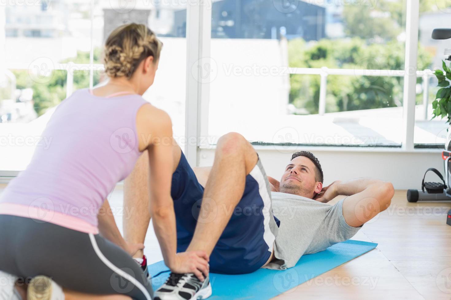 formateur aidant l'homme en forme à s'asseoir photo
