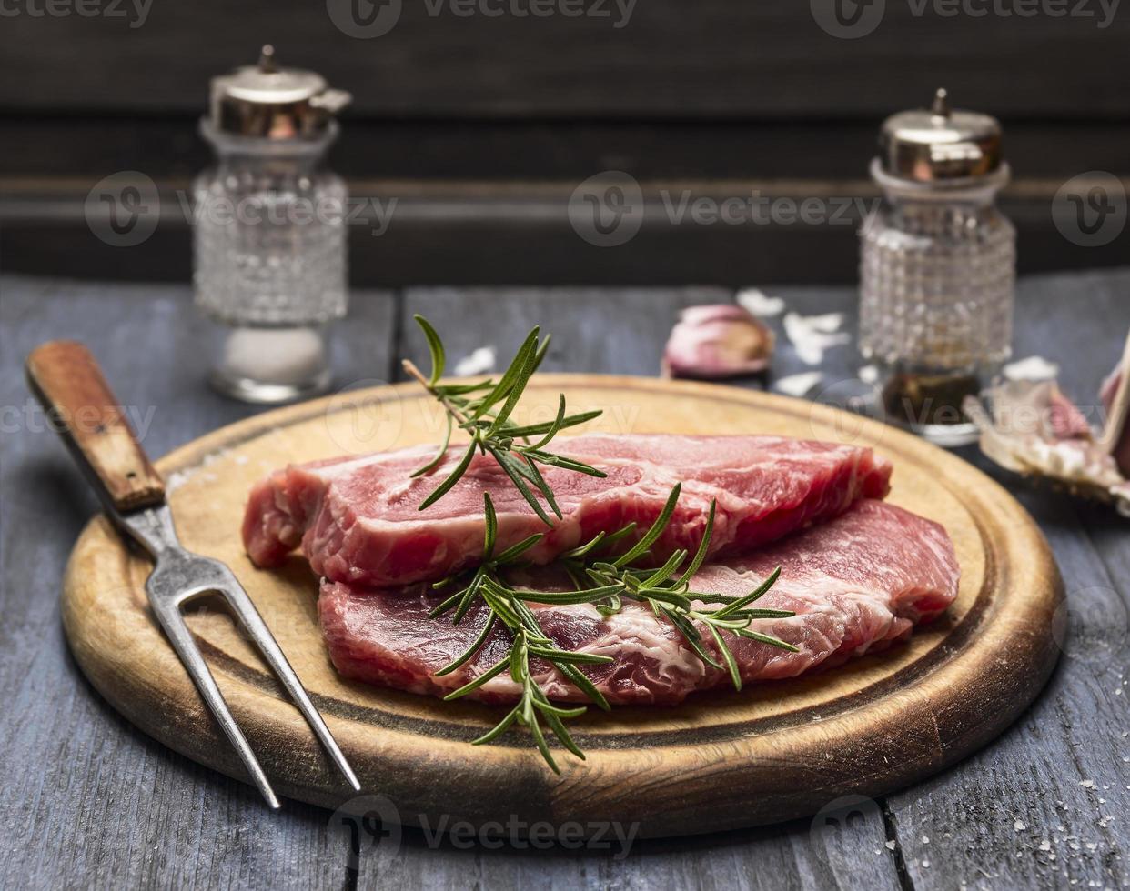 viande crue au romarin, ail, sel poivre fourchette de planche de bois photo