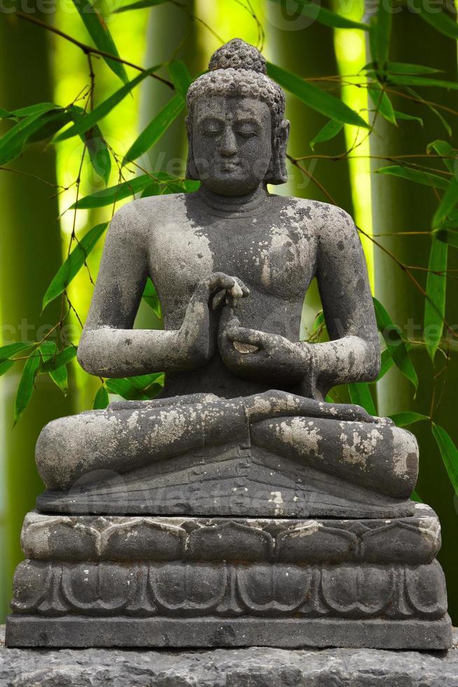 statue de Bouddha gris avec fond de bambou photo
