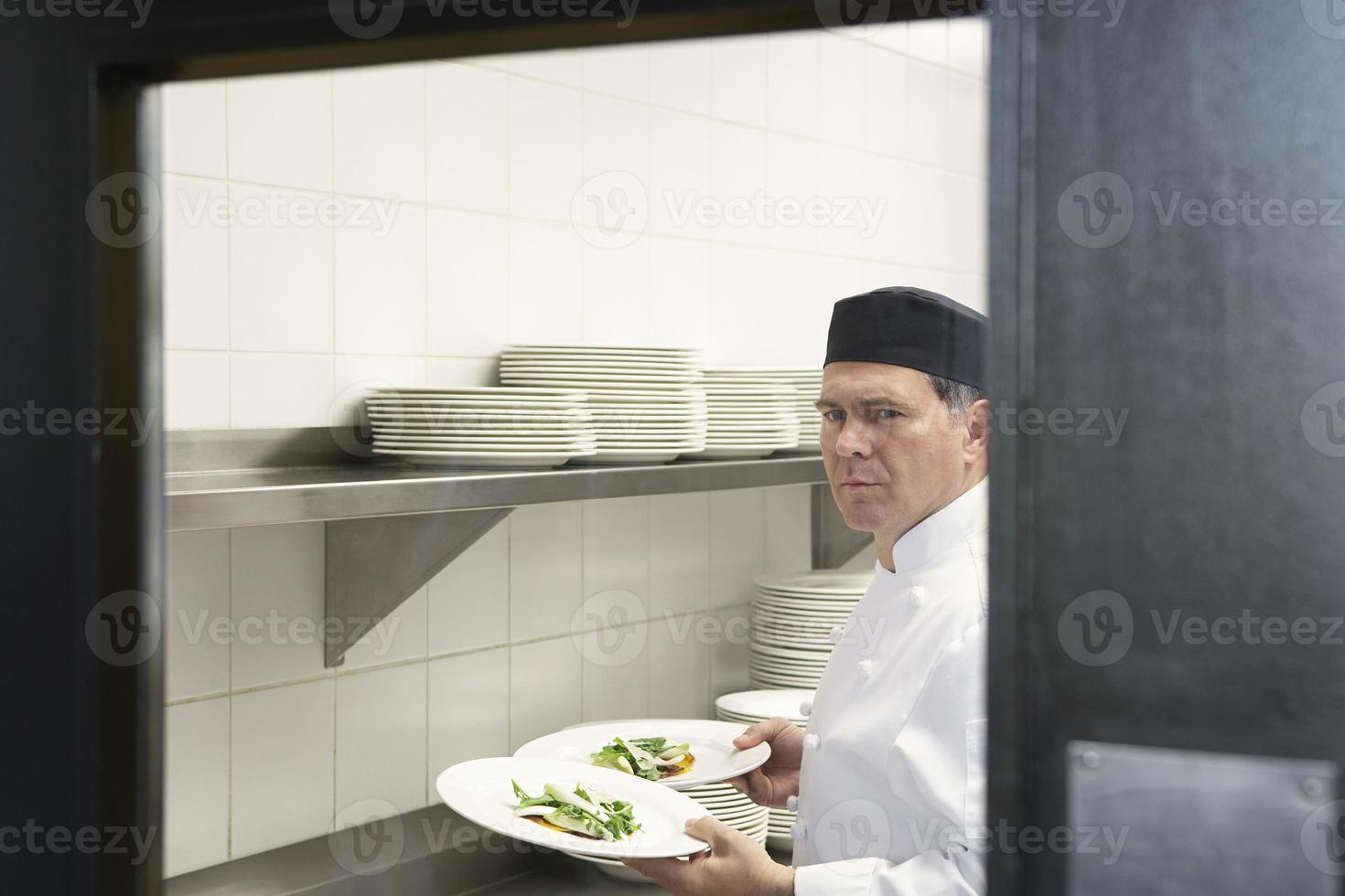 chef masculin avec des plats dans la cuisine photo