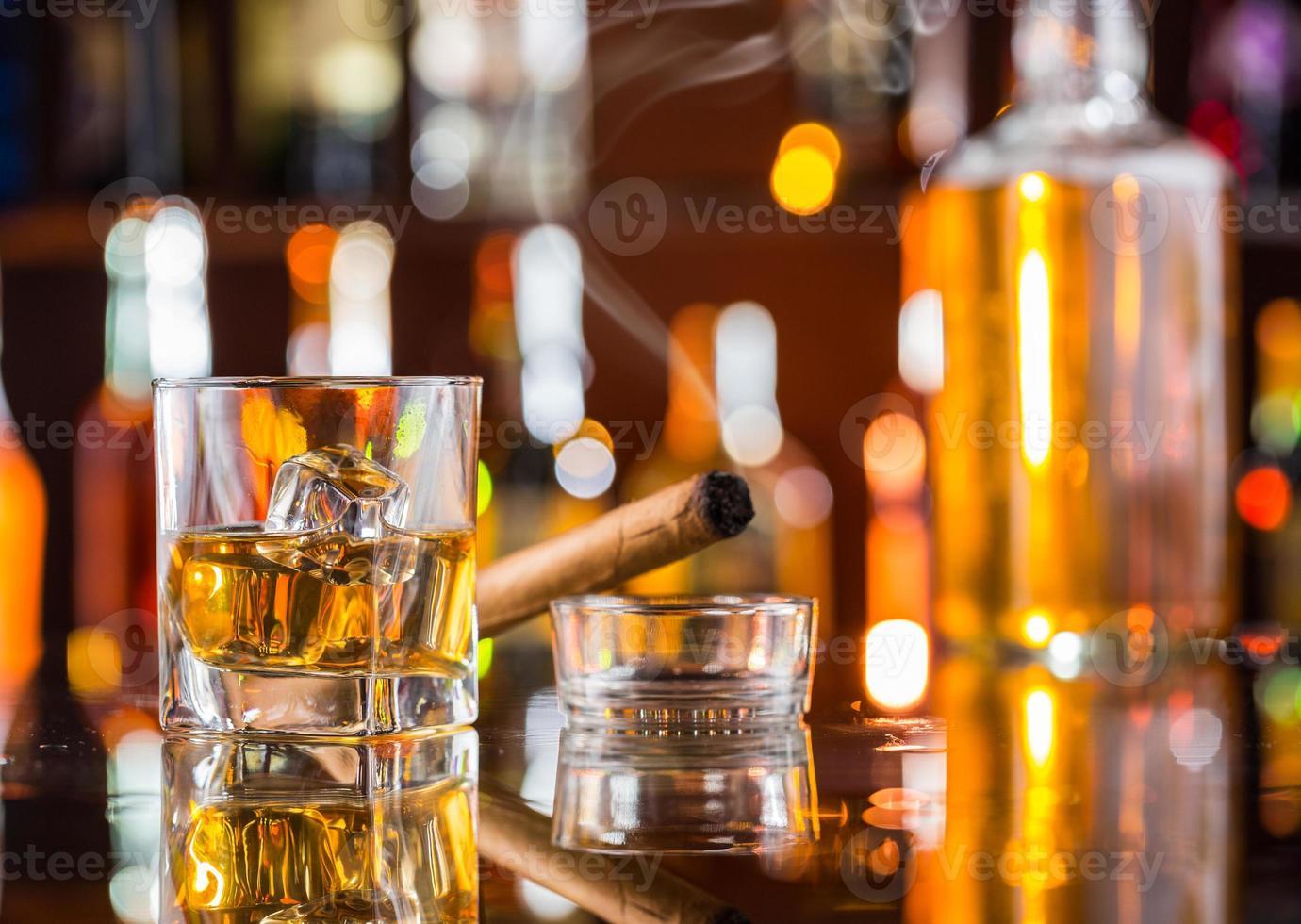 Boisson au whisky avec cigare fumant au bar photo