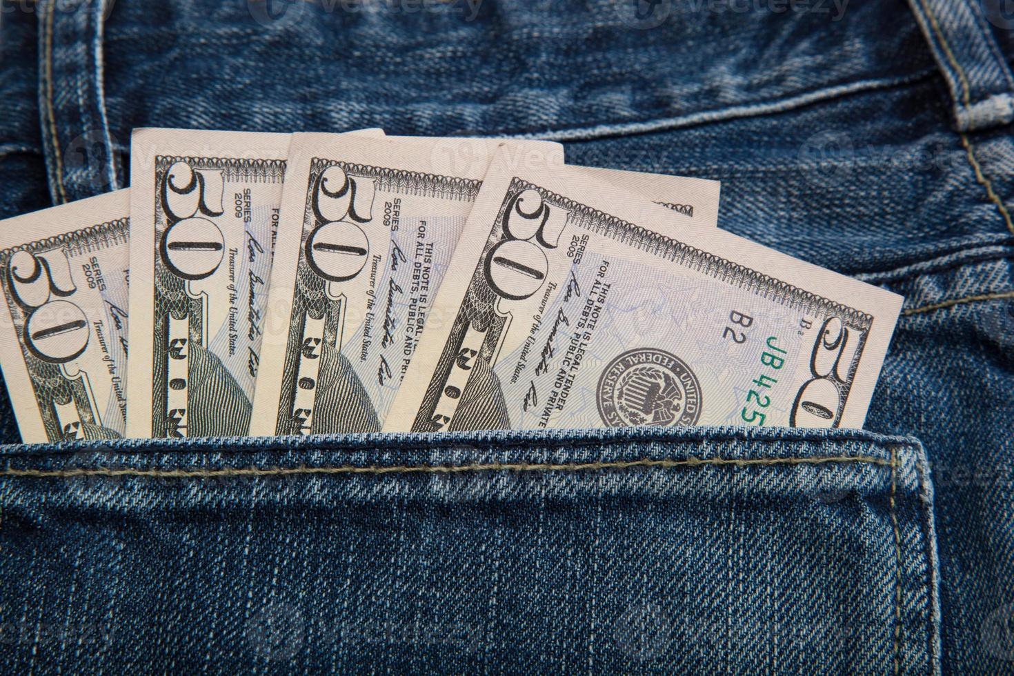 billets de banque dans la poche arrière de jeans. photo