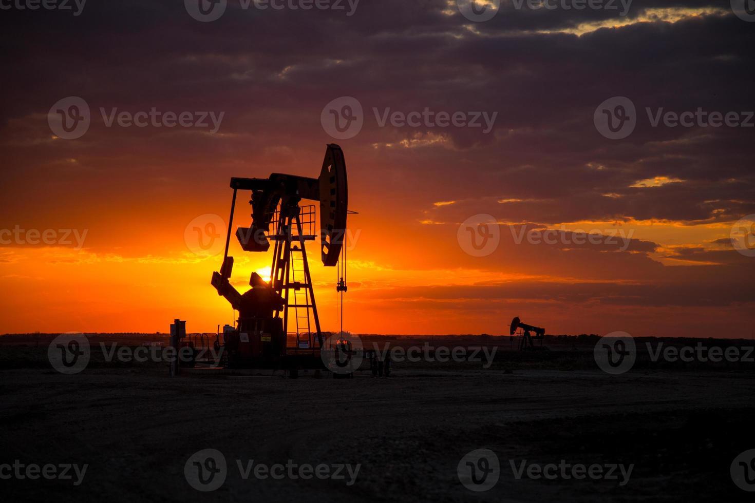 Pumpjacks champ pétrolifère au coucher du soleil photo