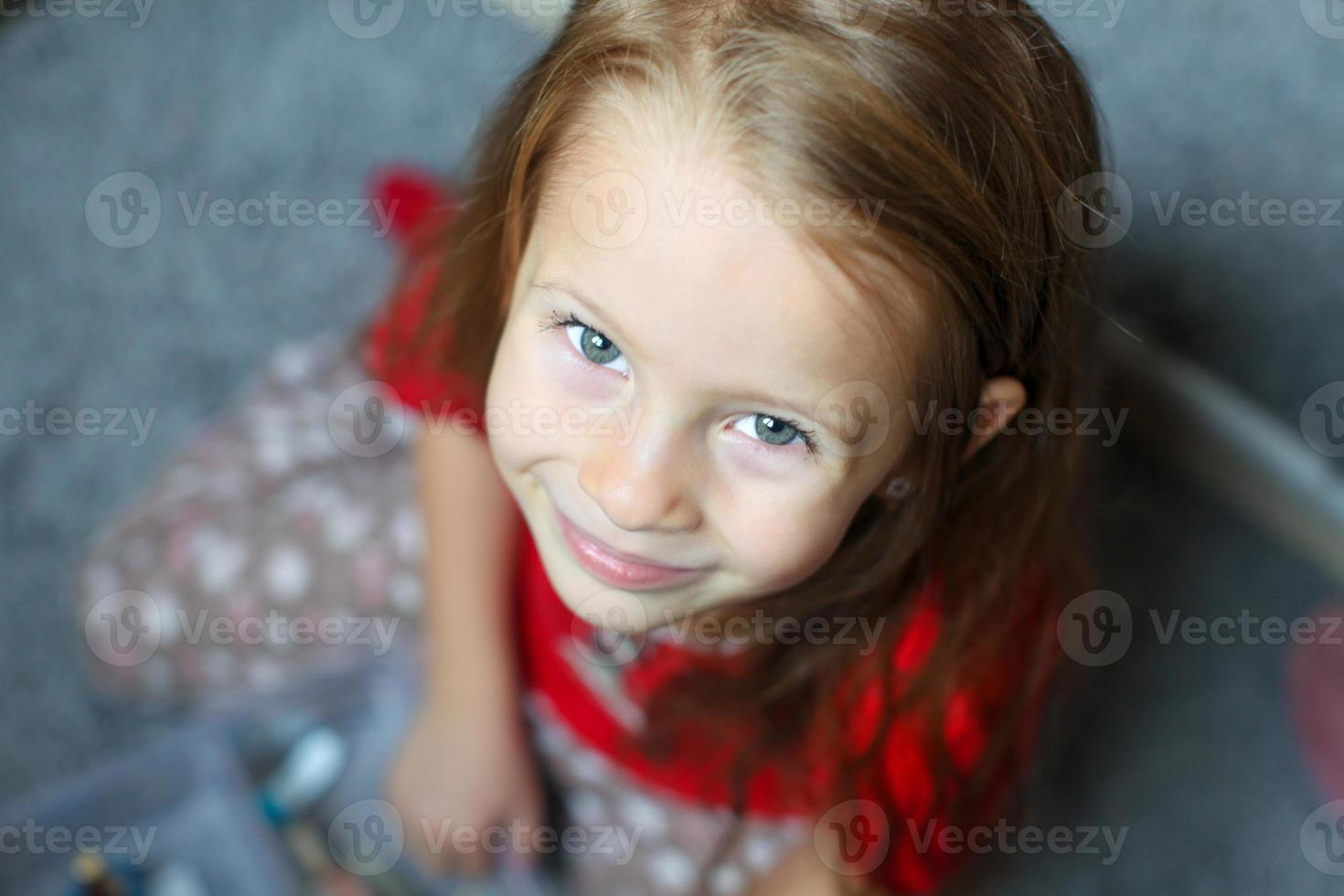 visage gros plan d'une belle petite fille mignonne aux yeux bleus photo