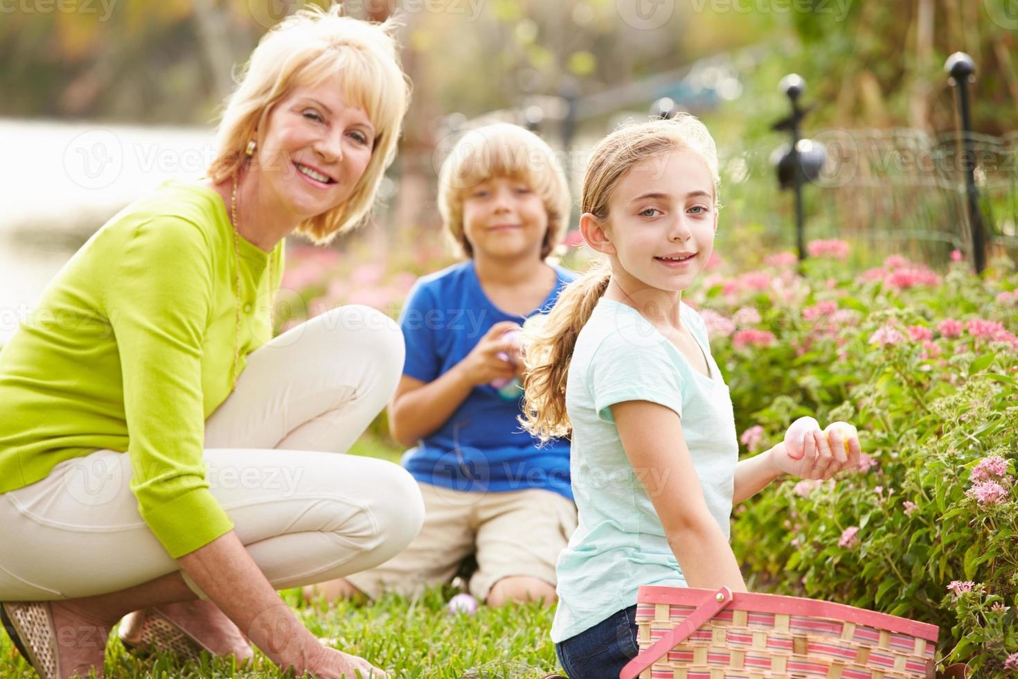 grand-mère avec petits-enfants sur la chasse aux oeufs de pâques dans le jardin photo