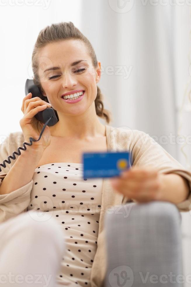 femme avec carte de crédit parler téléphone tout en étant assis sur le canapé photo