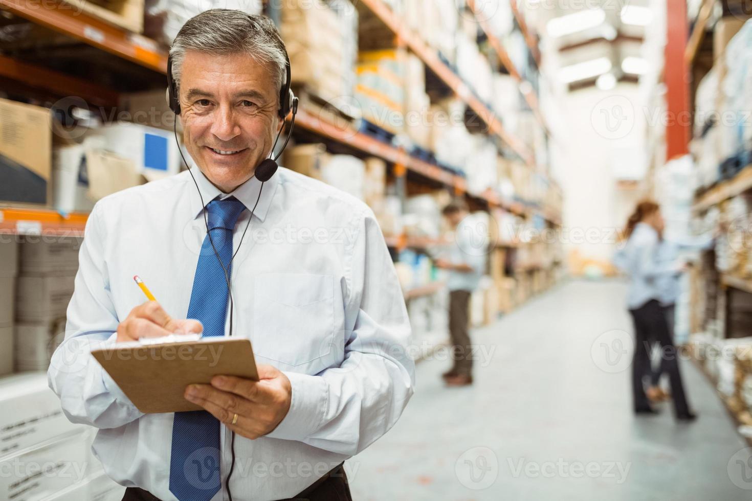 directeur d'entrepôt souriant écrit sur le presse-papiers photo
