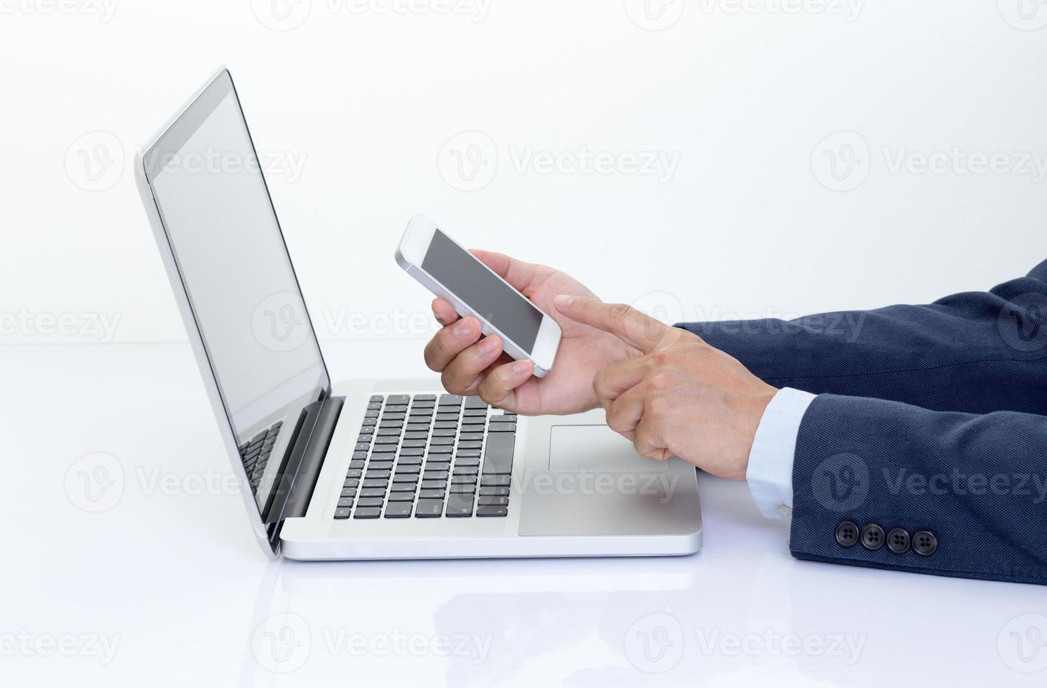homme d'affaires mains tenant un téléphone mobile avec ordinateur portable photo