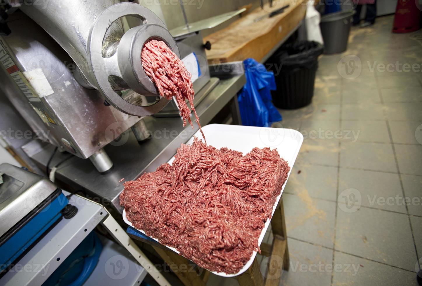 viande hachée tombant de la machine dans un récipient au magasin photo