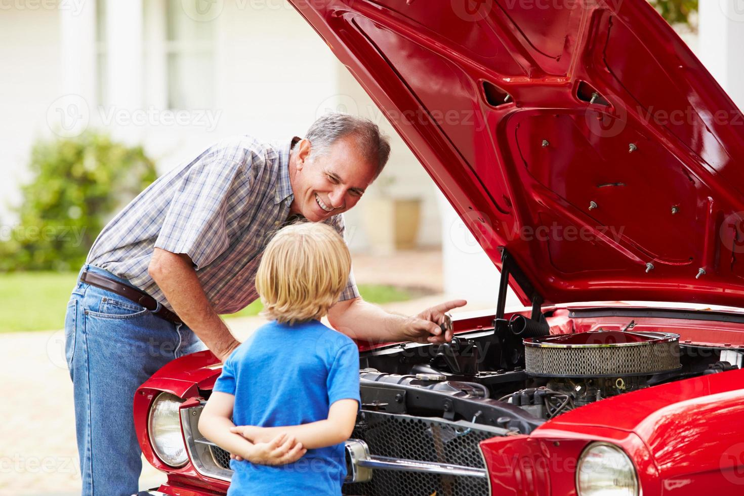 grand-père et petit-fils travaillant sur une voiture classique restaurée photo