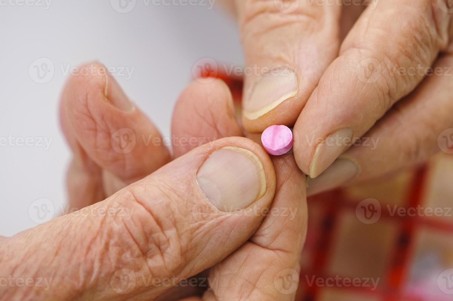 les mains âgées tiennent un comprimé rose entre les doigts photo