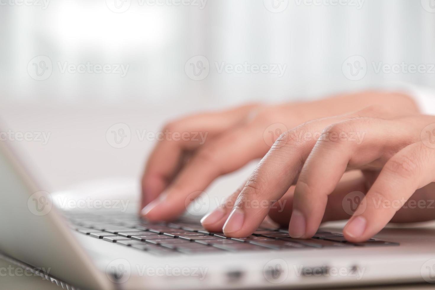 Gros plan de la main de femme d'affaires tapant sur le clavier d'ordinateur portable photo