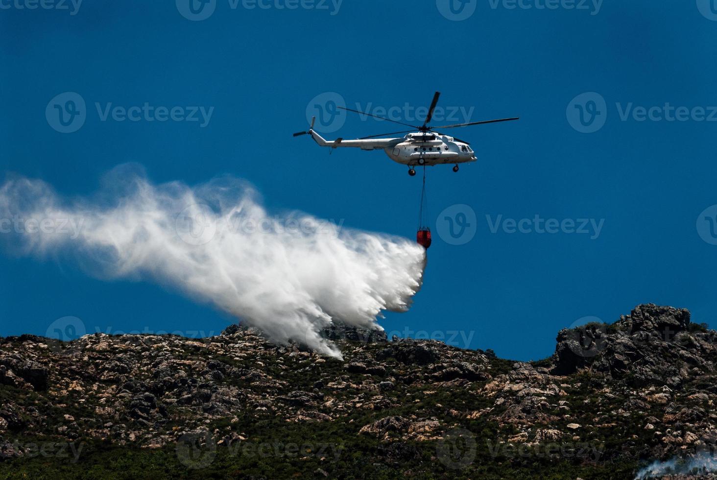 hélicoptère de lutte contre l'incendie laisse tomber la charge d'eau au sommet de la montagne. photo