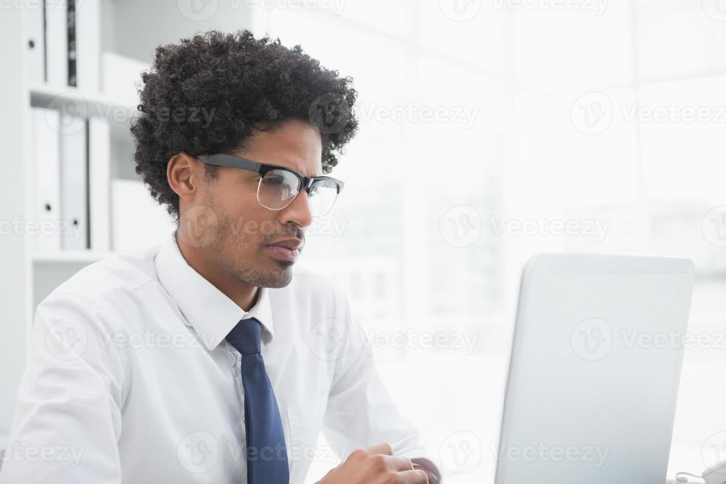 homme d'affaires concentré à la recherche de son ordinateur portable photo