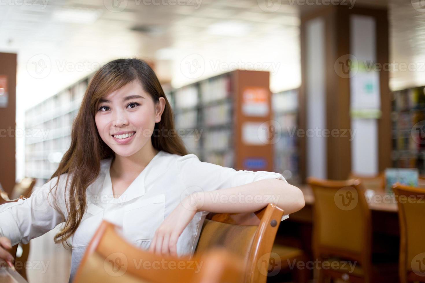belle étudiante asiatique utilisant un ordinateur portable pour étudier dans la bibliothèque photo