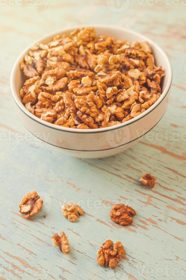 noyaux de noix dans un bol sur fond de bois rustique photo