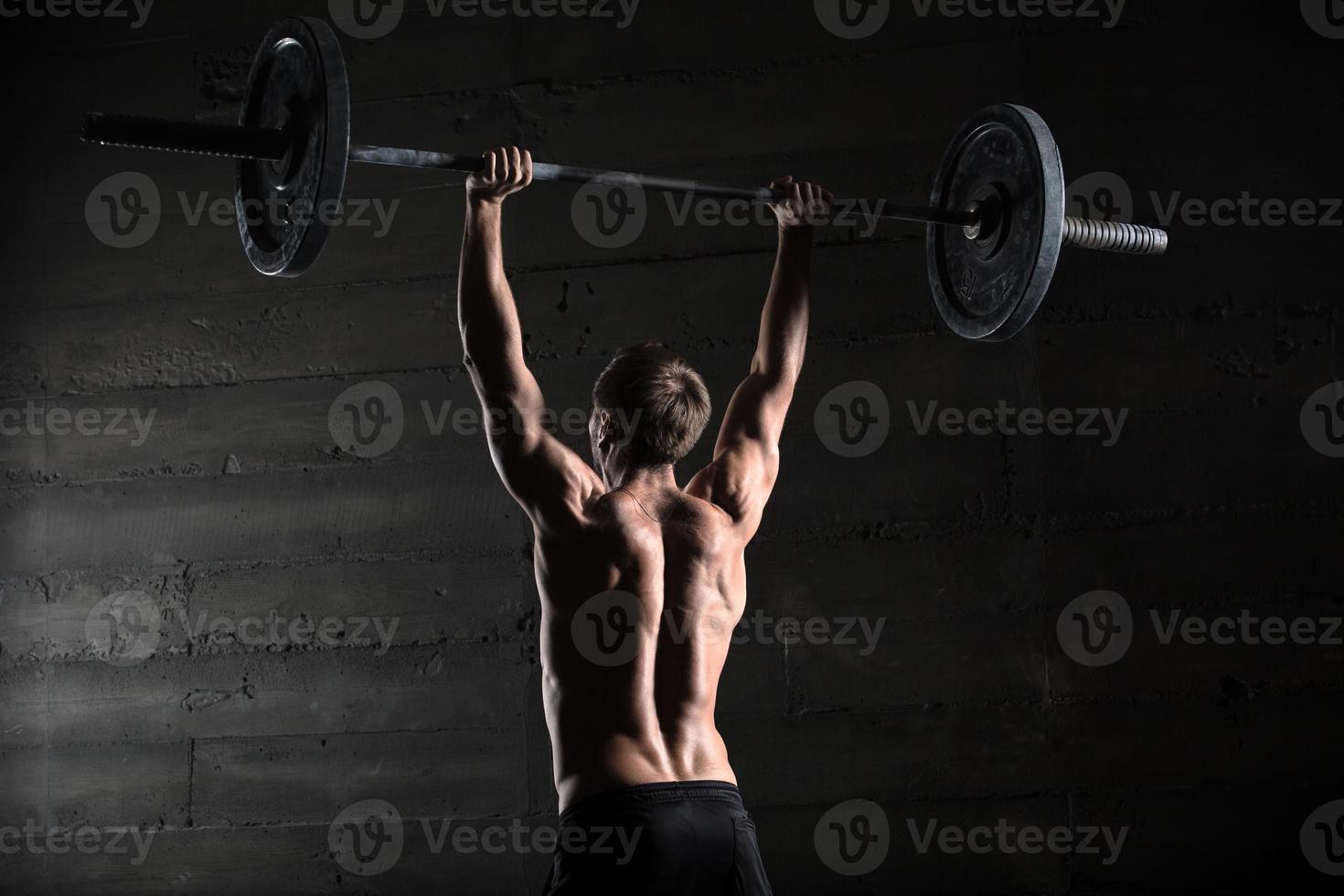portrait d'un bel athlète par derrière. athlète soulève le photo