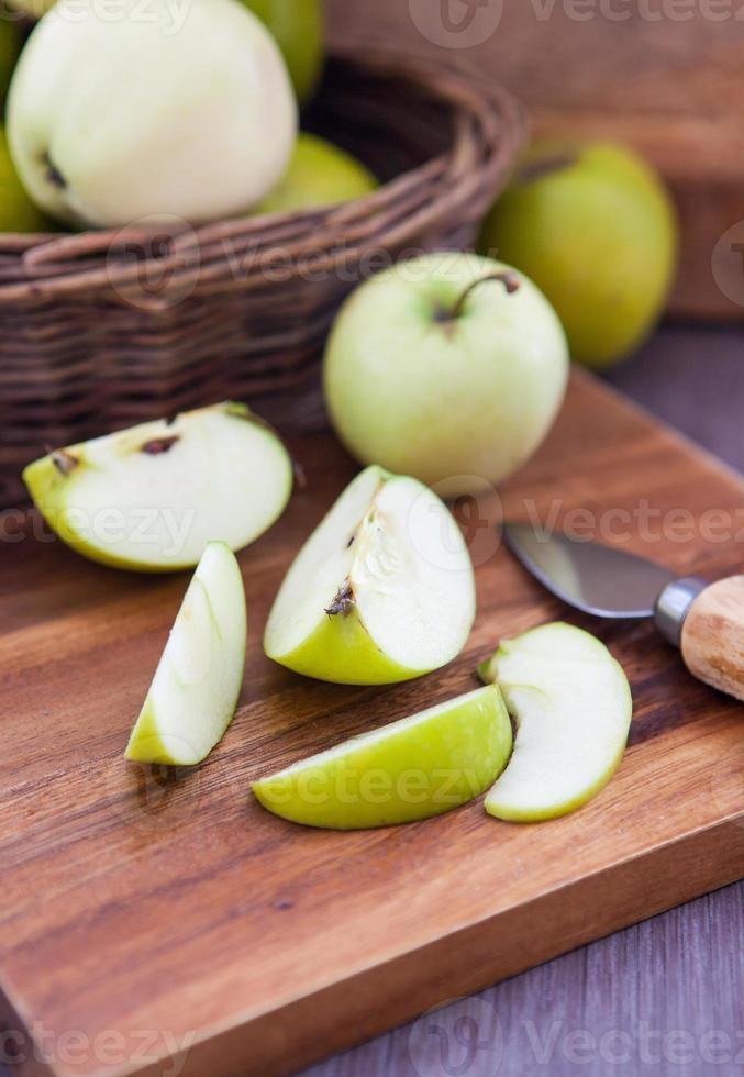 pomme verte tranchée sur une planche à découper en bois photo