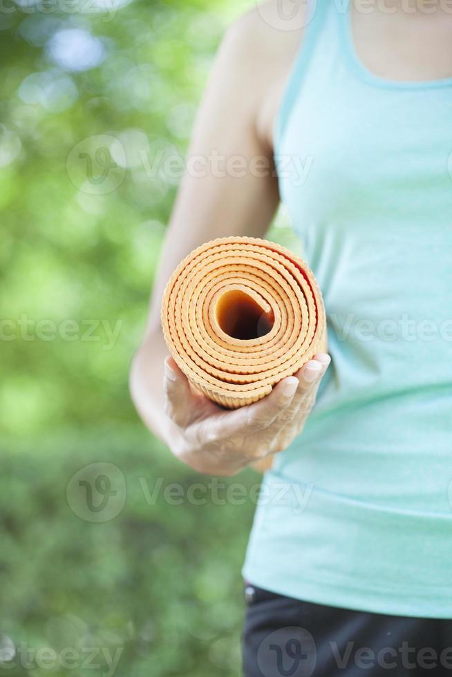jeune femme tenant un tapis de yoga photo