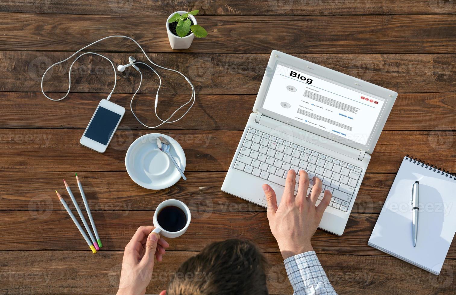 écrivain travaillant sur ordinateur au bureau en bois photo