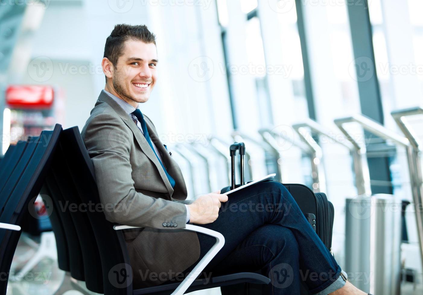 homme d'affaires moderne à l'aide de la tablette tactile à l'aéroport photo
