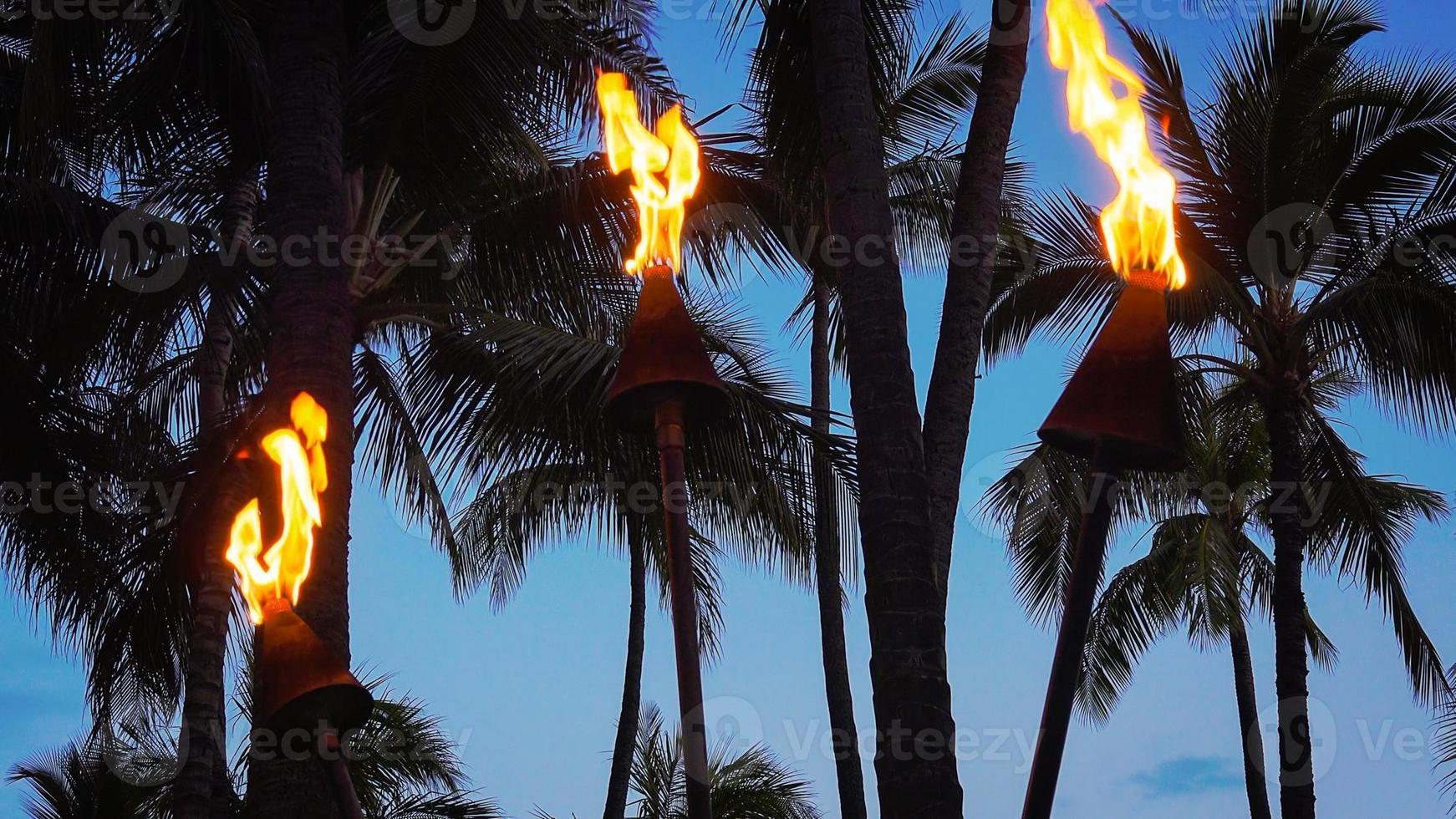 torches tiki brûlant sur la plage de waikiki la nuit photo